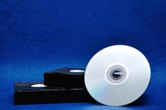 Two video cassettes with a CD. Two video cassettes isolated on a blue background with a cd stock photography