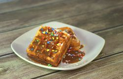 Two Viennese waffles in chocolate glaze with a sprinkle on a ceramic plate. Close-up stock photography