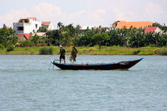 Two Vietnamese men fishing on the river Royalty Free Stock Image