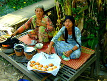 Two Vietnamese woman selling cakes in village. Woman cooking and selling cakes by the side of the road in a village in Vietnam Royalty Free Stock Images