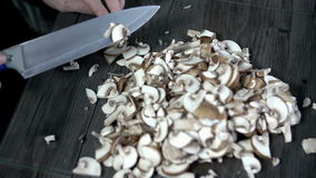 Two view of table full of sliced mushrooms. Slicing the porcinis into small slices and throwing them onto the frying pan stock video footage