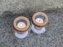 Two vigil candles burn on concrete sidewalk Stock Photography
