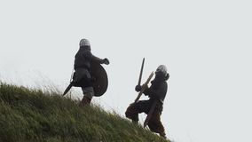 Two warriors Viking are fighting with swords and shields. Two Vikings are fighting in the meadow. Medieval Reenactment. Fog and wind in the meadow stock video footage