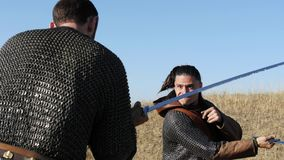 Two warriors Viking are fighting with swords in the meadow. Two Vikings are fighting in the meadow. Medieval Reenactment. View from behind stock video footage