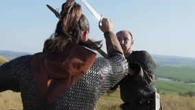 Two warriors Viking are fighting with swords in the meadow. Two Vikings are fighting in the meadow. Medieval Reenactment. View from behind stock video