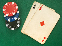 Two vintage aces and poker chips. Royalty Free Stock Photo