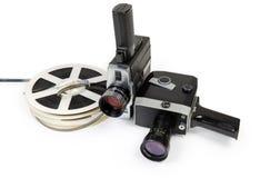 Two vintage amateur movie cameras and Super 8mm films reels. Two different vintage amateur film movie cameras and reels of color motion picture films Super 8mm stock images