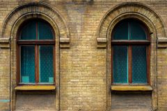 Two vintage arched windows in a wall of yellow bricks. Green - the colors of sea wave glass in a maroon dark red wooden. Frame. The concept of antique vintage Stock Photos