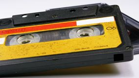 Two Vintage Audio Cassette Rotates on White Background. Transparent and yellow Retro tape cassette with a blank label. Old music. Close-up stock video footage