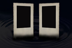 Two vintage bevelled photo frames on the black. Two vintage bevelled photo frames with jagged edges partially submerged in the water, which forms a circle wave stock images