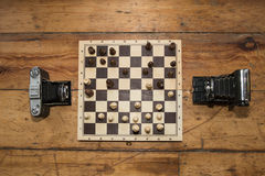 Two vintage cameras  playing chess on a wooden board set on some. Wooden floor. check Mate Royalty Free Stock Image