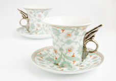 Two vintage cups with handles in form of wings. On saucers royalty free stock image