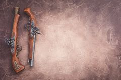 Two vintage duel pistols on wooden background royalty free stock photo