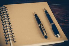 Two vintage fountain pens over a dairy book. On wood table stock image