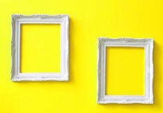Two vintage frames on yellow wall. Two white vintage frames on yellow wall Stock Images