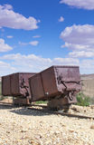 Two vintage gold & silver ore carts. Two red rusted vintage gold/silver ore cart abandoned in Nevada desert stock photos