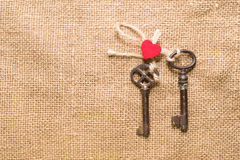 Two vintage key and a red heart on old cloth Stock Photography