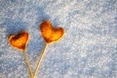 Two vintage orange tangerine hearts on white snow Royalty Free Stock Photo