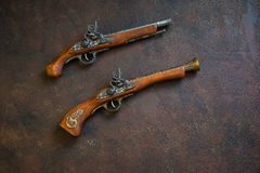 Two vintage duel pistols on wooden background royalty free stock image