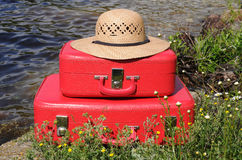 Two vintage red suitcases and sun hat. Two old red suitcases and sun hat amongst wild flowers on water edge Royalty Free Stock Image