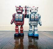 Two vintage robot toy happy together on a wooden floor. With reflection Royalty Free Stock Images