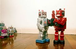 Two vintage robots fight it out. On old fooden floor stock image