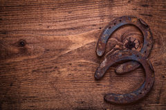 Two  vintage rusted horseshoes on old wooden board Royalty Free Stock Photography