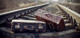 Two vintage suitcases lie on railway rails. Stock Photo