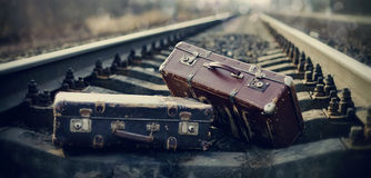 Two vintage suitcases lie on railway tracks. Royalty Free Stock Images