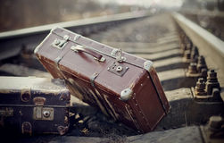 Two vintage suitcases on rails Stock Photography
