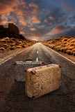 Two vintage suitcases on road through desert Royalty Free Stock Photography