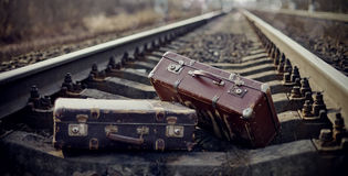 Two vintage suitcases thrown on railway rails. Royalty Free Stock Images