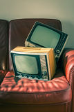 Two vintage televisions on red couch Royalty Free Stock Photo