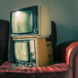 Two vintage televisions on red couch Stock Photos