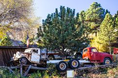 Two Vintage Trucks In Salvage Yard. Two Vintage Trucks Parked On Ramps In Old Salvage Yard Royalty Free Stock Photos