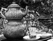 Two vintage Turkish teapots with glass cup, in black and white. Two vintage engraved copper Turkish teapots with double stacked kettles allowing tea to be brewed Royalty Free Stock Photo