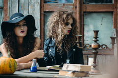 Two vintage witch sitting at the table Stock Images