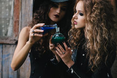Two vintage witches perform magic ritual. With elixir in hand on the eve of Halloween Stock Photography