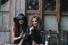 Two vintage witches perform magic ritual. With elixir in hand on the eve of Halloween Royalty Free Stock Photo