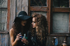 Two vintage witches perform magic ritual. With elixir in hand on the eve of Halloween Stock Photo