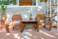 Two vintage wooden chairs on cement porch and polished cement wall front of house royalty free stock photography