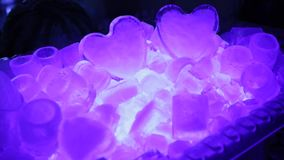 Two violet ice heart in dark.  stock video footage