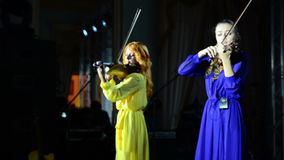 Two violinists play music on stage. The concert of contemporary music on a violin stock video footage