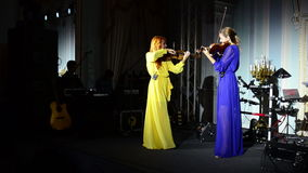 Two violinists play music on stage. The concert of contemporary music on a violin stock footage