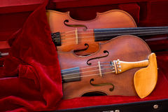 Two violins covered by cloth in a case. Two violins covered by red cloth in a violin case Royalty Free Stock Image