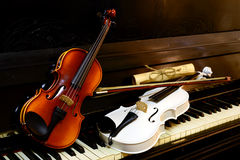 Two violins different colors on the piano Royalty Free Stock Photography