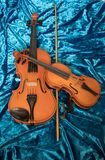 Two violins of different sizes on blue fabric stock photography