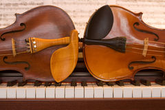 Two violins lying on a piano keyboard. Side by side Stock Images