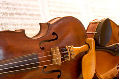 Two violins lying side by side. With sheet music behind Royalty Free Stock Photo