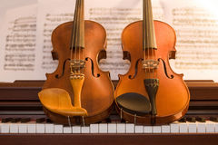 Two violins on top of piano keys. Two violins resting on top of piano keys Royalty Free Stock Photography